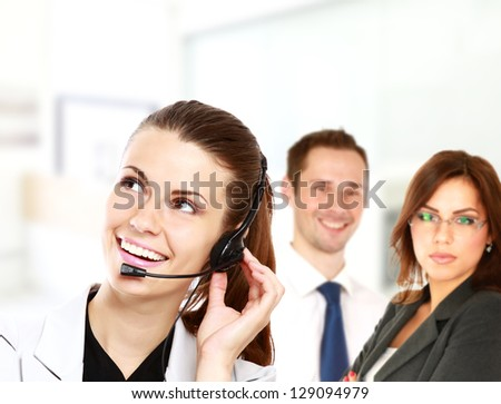 Smiling business woman with headset and business team