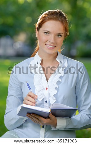 Smiling business woman with notebook in the city garden