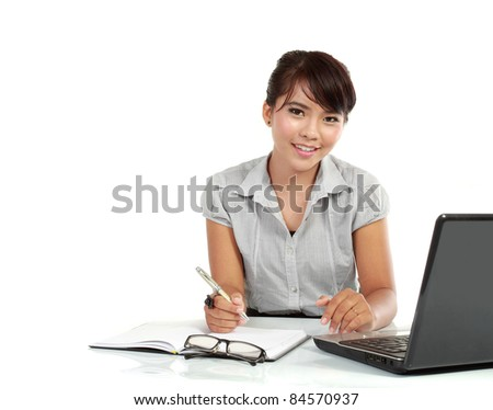 smiling business woman working at her desk with a laptop and paperwork