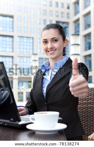 smiling business woman working on laptop and shoving thumbs up - stock photo