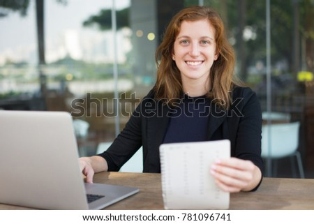 Smiling Business Woman Working on Laptop at Cafe