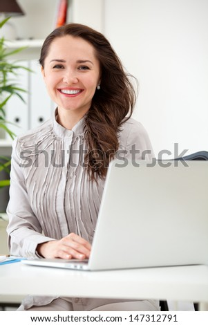 Smiling business woman working on laptop computer at office - stock photo