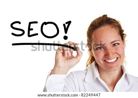 Smiling business woman writing the word SEO with pen - stock photo