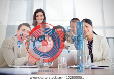 Smiling business workers looking at chart interface in a meeting