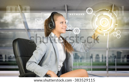 Smiling businesslady touching holographic screen