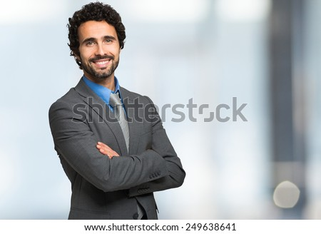 Smiling businessman against a bright background - stock photo