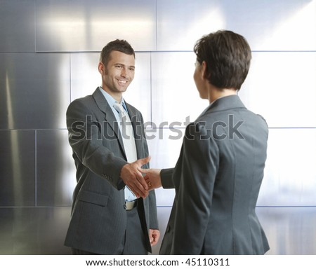 Smiling businessman and businesswoman shaking hands in modern design office.