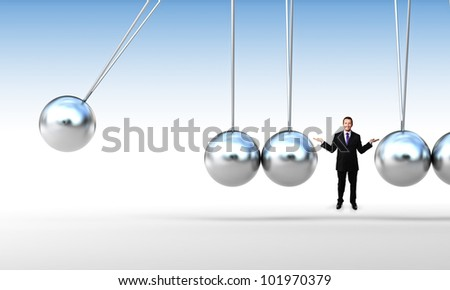 smiling businessman and classic newton cradle - stock photo