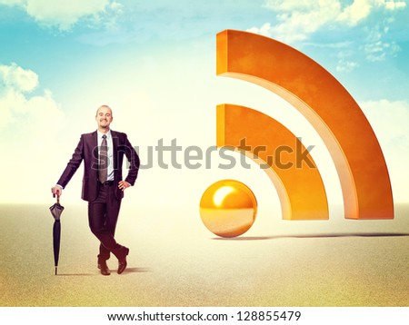 smiling businessman and 3d huge rss logo - stock photo