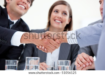 Smiling businessman and his colleague closing a deal with a partner in a meeting - stock photo