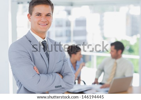 Smiling businessman and his colleagues in background in the office - stock photo