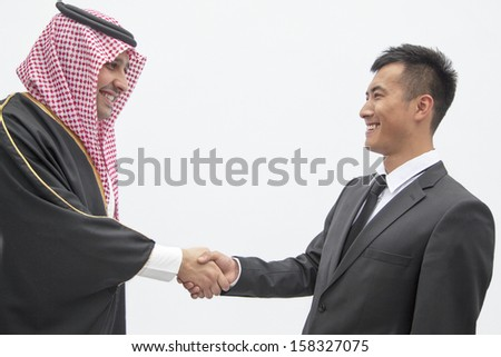 Smiling businessman and young man in traditional Arab clothing shaking hands - stock photo
