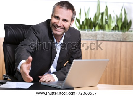 Smiling businessman behind  office desk stretching out hand for handshake, closing a business deal or agreement. - stock photo