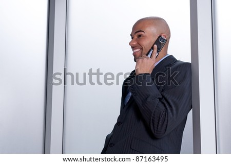 Smiling businessman beside an office window, talking on his cell phone.