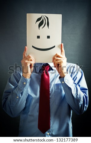 Smiling businessman. Businessman in blue shirt holding white paper card with happy face on it - stock photo