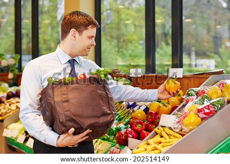 Smiling businessman buying fresh vegetables in an organic food store - stock photo