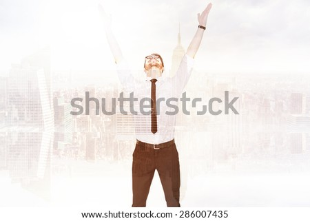 Smiling businessman cheering with his hands up against room with large window looking on city - stock photo