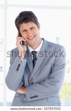 Smiling businessman crossing his arms while talking on the phone - stock photo