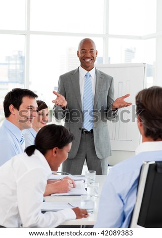Smiling businessman doing a presentation to his colleagues in the office - stock photo