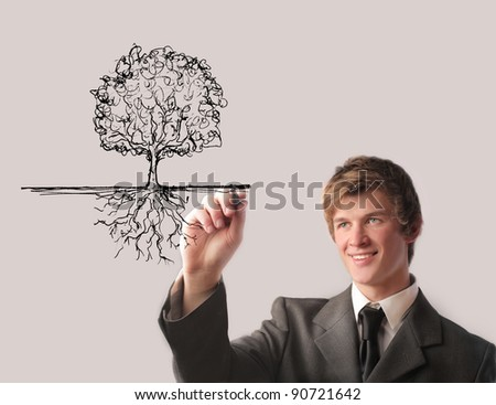 Smiling businessman drawing a tree - stock photo