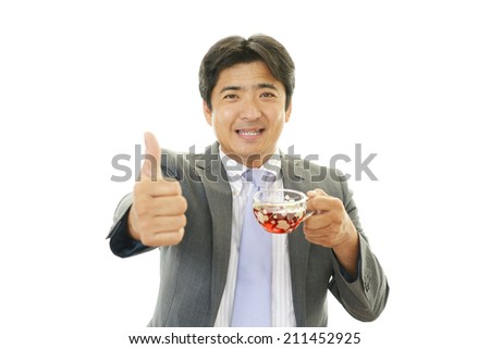 Smiling businessman drinking tea.