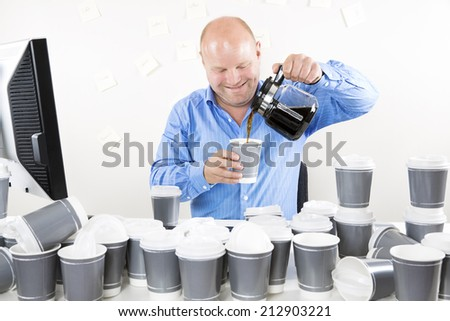 Smiling businessman drinks too much coffee - stock photo