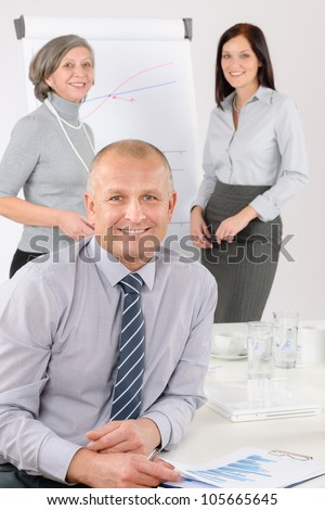 Smiling businessman during team meeting with colleagues give presentation