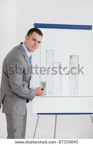 Smiling businessman editing diagram - stock photo