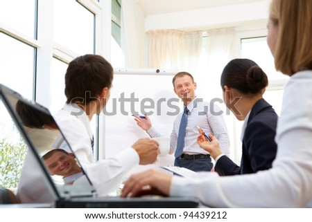 Smiling businessman explaining business ideas to his partners - stock photo