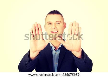Smiling businessman gesturing stop sign - stock photo