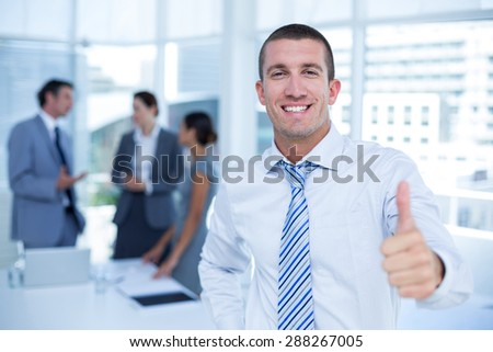 Smiling businessman gesturing thumbs up in his office - stock photo