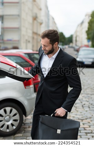Smiling businessman getting his briefcase from the boot of his car as he arrives at work in the morning - stock photo