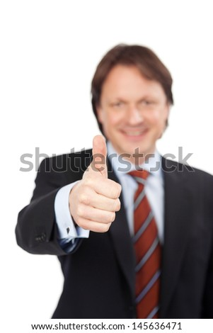 Smiling businessman giving a thumbs up gesture of approval, agreement and success with selective focus to his hand - stock photo