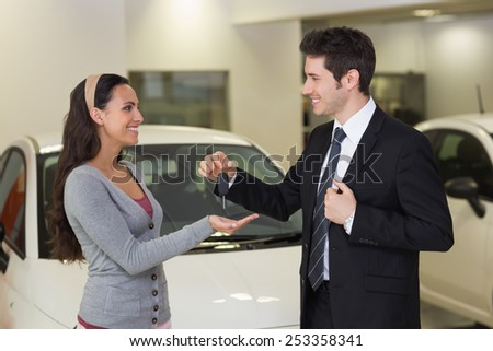 Smiling businessman giving car key to happy customer at new car showroom - stock photo