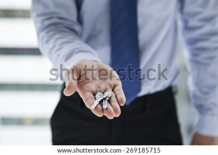 Smiling businessman giving keys to you - stock photo