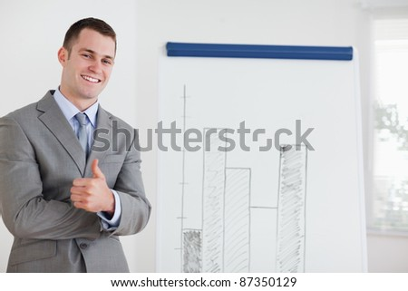Smiling businessman giving thumb up next to diagram - stock photo