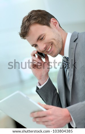 Smiling businessman having a phonecall in building hallway - stock photo