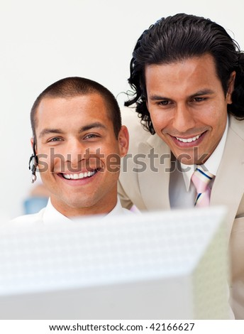 Smiling businessman helping his colleague at a computer in the office