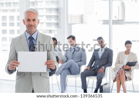 Smiling businessman holding a blank sign with people waiting behind - stock photo