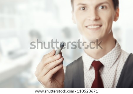 Smiling businessman holding a pen at his office - stock photo