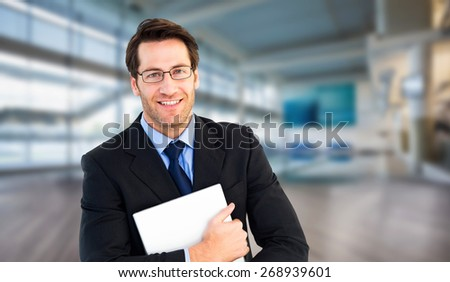 Smiling businessman holding his laptop looking at camera against fitness studio - stock photo