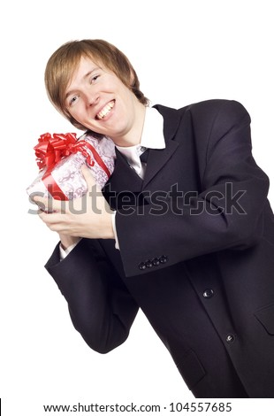Smiling businessman holding present with ribbon - stock photo