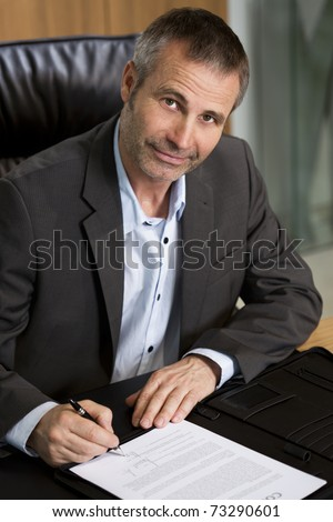 Smiling businessman in dark suit and blue shirt sitting at office desk and signing a contract, looking up. - stock photo