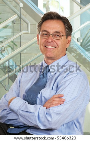 Smiling businessman in modern interior setting with staircase - stock photo