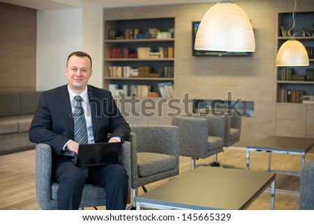 Smiling businessman in suit and tie sitting on a chair with a laptop