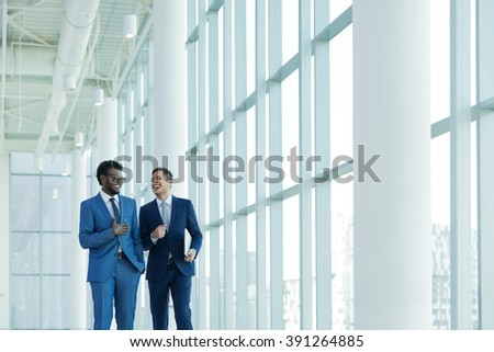 Smiling businessman in suit in office - stock photo