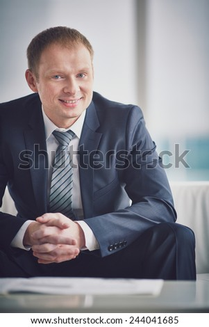 Smiling businessman in suit looking at camera - stock photo