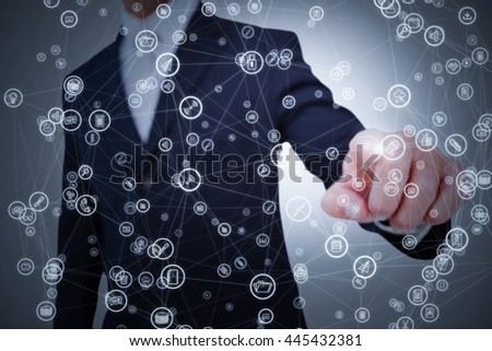 Smiling businessman in suit pointing against grey background