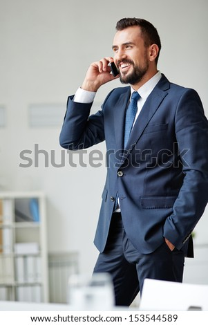 Smiling businessman in suit speaking on cellular phone - stock photo