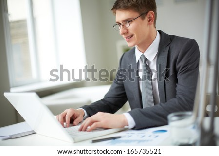 Smiling businessman in suit typing on laptop in office - stock photo